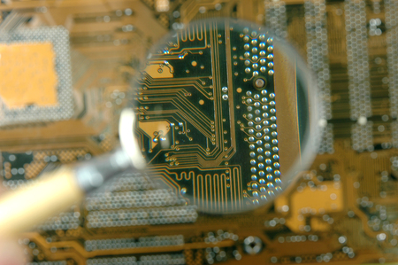 printed circuit board and magnifying glass Stock Photo