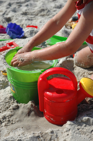 young child playing wet sand in plastic bucket photo