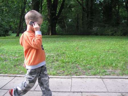 sidewalk talk: young child walks with mobile phone