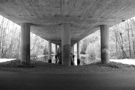 Huge columns holding up a concrete bridge. B&W