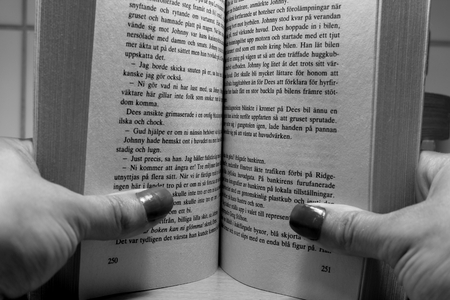 Hands holding an open book. Reading a book. Black and white.