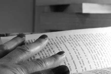 Finger with painted nails spread out over a book page. Black and white.