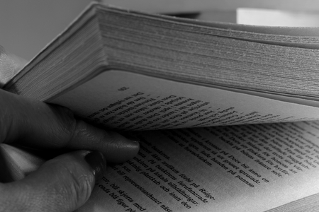 Two fingers in between book pages. Black and white. Stock Photo