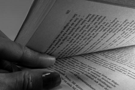 Two fingers in between book pages. Opening a book.