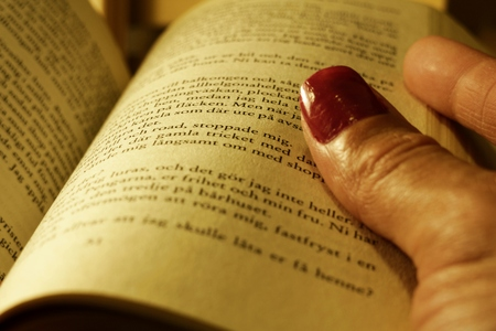 Han holding an open book. Finger with painted nails. Close up Stock Photo