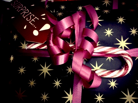 Close up on wrapped christmas present with gift tag and candy cane decor