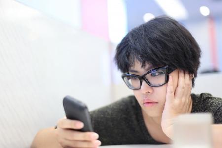 Kort Haar Meisje uitziende mobiele telefoon en ongelukkig voelen Stockfoto