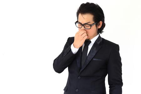 De Aziatische zakenman die zijn neus houdt.