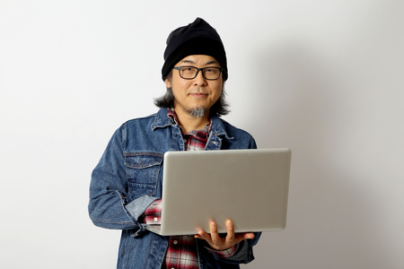 The Asian man with denim shirt and beanie standing on the white background.