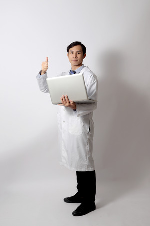 The Asian doctor standing on the white background. 写真素材
