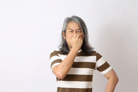 The senior Asian man standing on the white background.