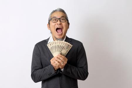 Der asiatische Mann, der Geld auf dem weißen Hintergrund hält.