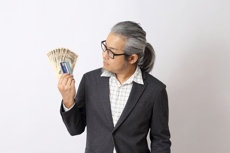 The Asian man holding money on the white background. Фото со стока