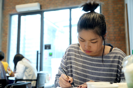 The Asian woman learning japanese language in the coffee shop.