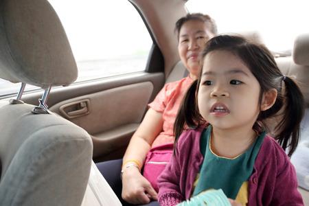 La familia asiática en el asiento trasero del coche. Foto de archivo