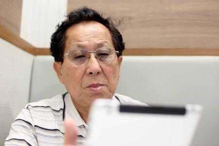 The Asian elder man using tablet.