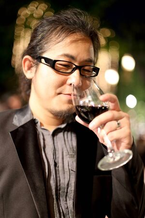 The Asian man drinking red wine in the night party.