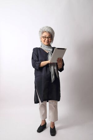 The elder Asian woman on the white background. Stock Photo