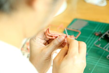 The Asian man doing on plastic model as his hobby.
