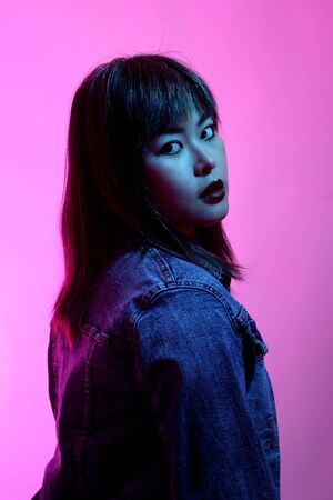 The Asian woman posing on the white background with the gel color light.