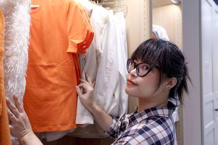 Die asiatische Frau, die Kleidung im Kleiderschrank auswählt.