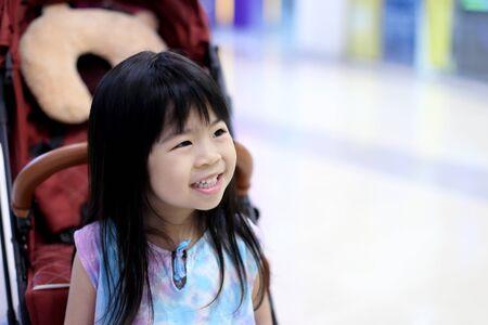 Młoda Azjatycka dziewczyna siedzi w wózku dziecięcym. Zdjęcie Seryjne