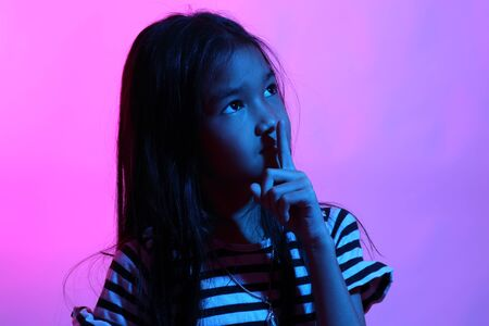 The Asian girl posing in the color gel light. Stockfoto
