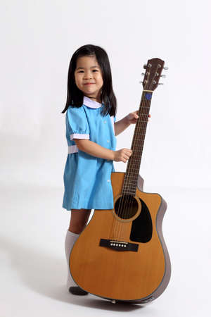 The young Asian girl with acoustic guitar on the whit background.