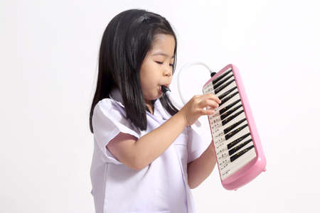 The young Asian girl playing melodion.