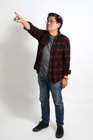 The senior Asin man in in casual clothes on the white background.