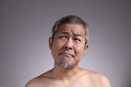 The Portrait of Asian man on the grey background.