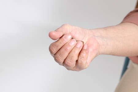 The Asian elder female massaged her hand by wooden ball.
