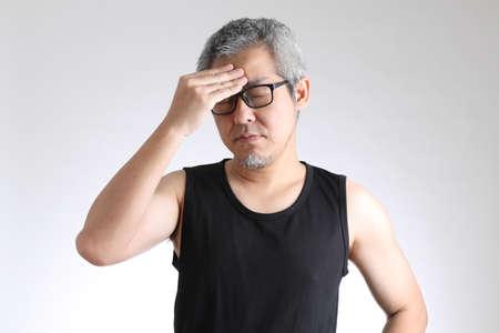 The elder Asian man in sport uniform standing on the white background.