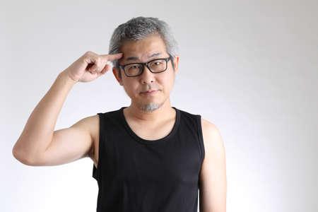 The elder Asian man in sport uniform standing on the white background. Stock fotó