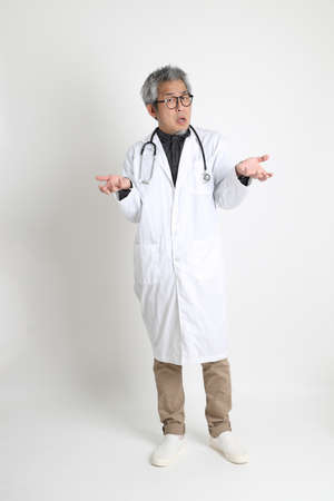 The senior Asian physician on the white background.