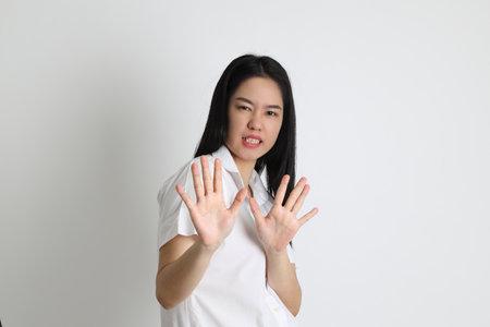 The Asian girl in university uniform standing on the white background. Imagens