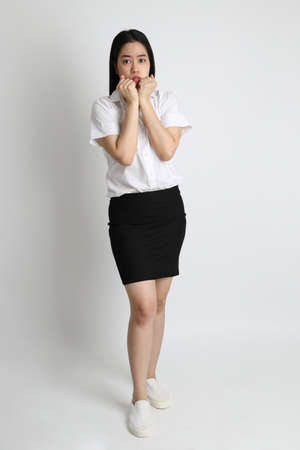 The Asian girl in university uniform standing on the white background.
