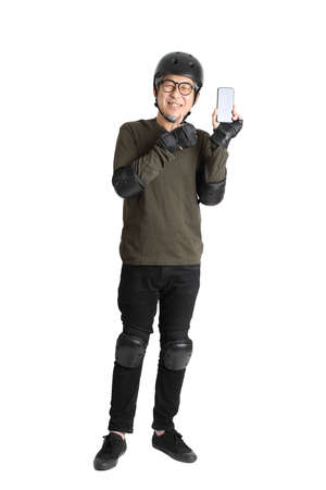 The Asian man with protective gear standing on the white background.
