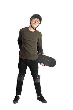The Asian man with protective gear and skateboard standing on the white background. Reklamní fotografie
