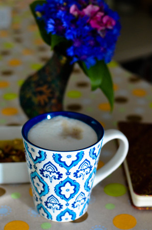 A cup of hot coffee with milk, flowers, honey and book. Romantic background with retro filter effect Stock Photo
