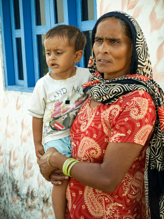 disadvantaged: Amroha, Uttar Pradesh, INDIA - 2011 :Rural Indian woman with child in hands and in red sari portrait