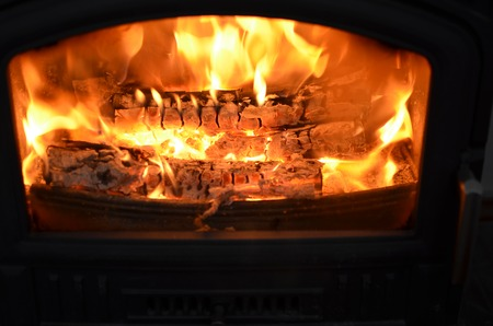 fireplace home: Log fire in a black fireplace at home Stock Photo