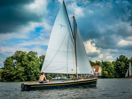 Small white sail yacht sailing in the lake near Groningen, Netherlands