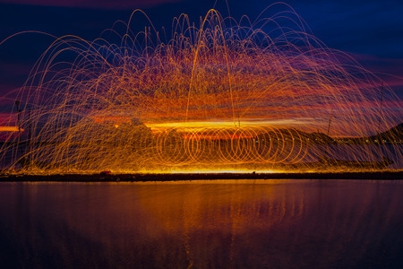 incendiary: Firework showers of hot glowing sparks from spinning steel wool on the beach. Stock Photo