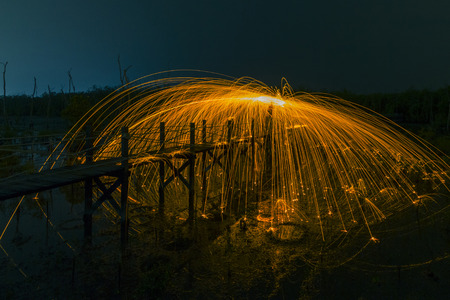 Firework showers of hot glowing sparks from spinning steel wool on the beach. Imagens