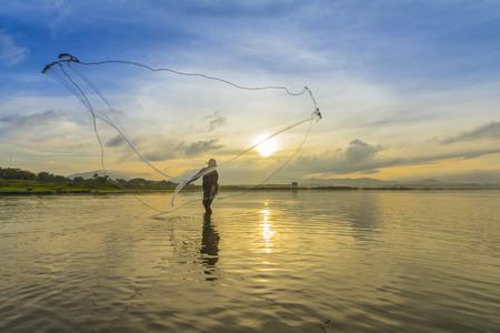 commercial fishing net: A man throwing fishing net during sunrise