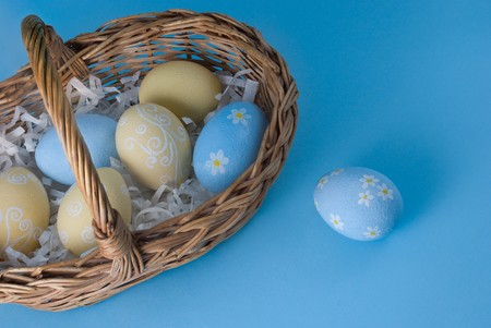 Easter eggs with basket on blue background