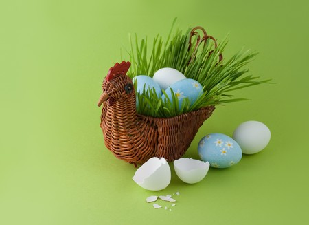 Easter eggs with basket on green background