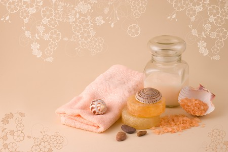 Jar with a pink cream, soap, pink towel and scattered orange sea salt on a beige background Stock Photo
