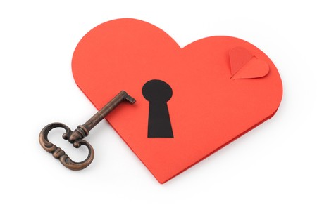 Key and paper heart on white background